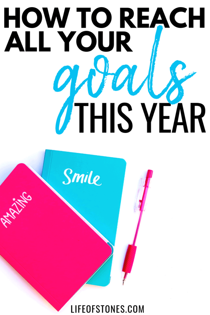 Pink and blue notebooks with a pen and text that reads: How to reach all your goals this year
