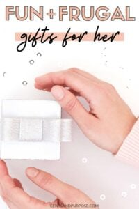 Women's hands and forearms with pink sleeves opening a small white gift box and text that reads: Fun and frugal gifts for her