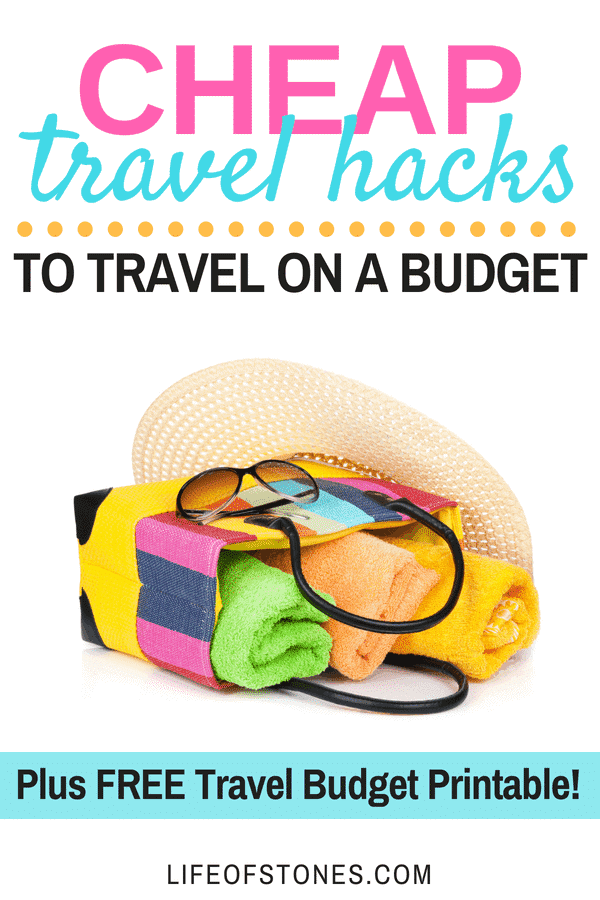 Beach bag laying on its side with colored towels, sunglasses and a beach hat and text that reads: Cheap travel hacks to travel on a budget plus a free travel budget printable