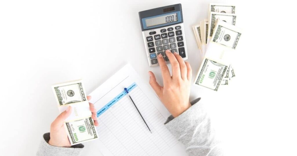 Hands with money, worksheet and calculator